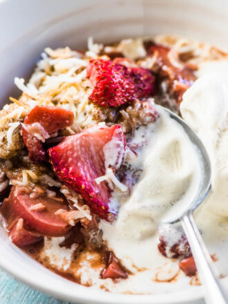 A close up of a spoon in a bowl of strawberry rhubarb cobbler with some vanilla ice cream.