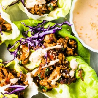A close up of these Thai turkey lettuce wraps with tahini sauce drizzled over the top.