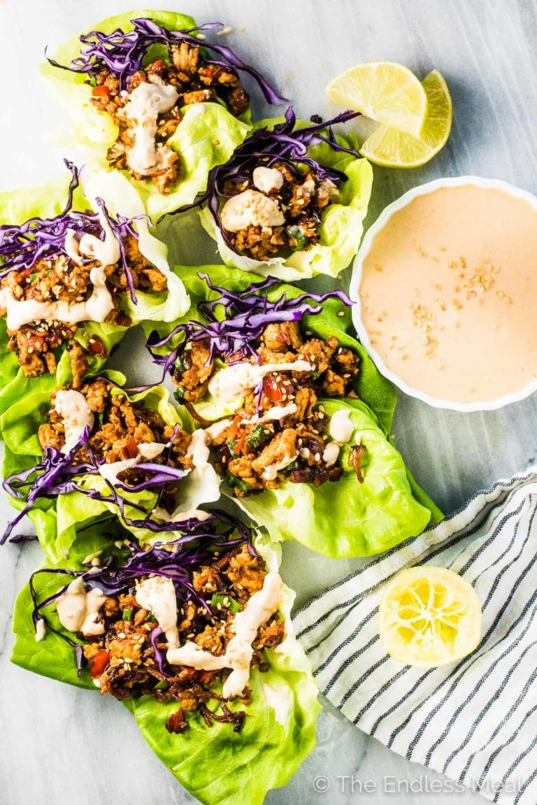 Turkey taco lettuce wraps on a marble board with some creamy ginger tahini sauce on the side.