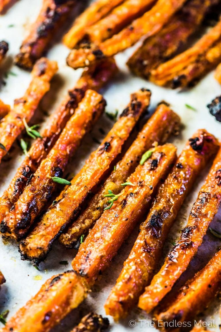 Baked carrot fries looking nice and crispy on a baking sheet.
