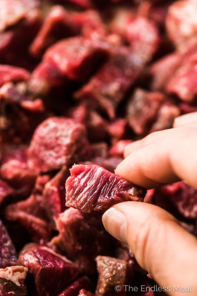 A hand holding up a piece of raw beef to show the perfect size to cut it for this beef soup.