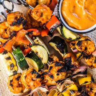 Grilled shrimp skewers on a white plate with veggies and roasted red pepper dip.