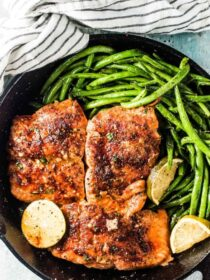 Honey salmon in a cast iron pan with green beans on the side.
