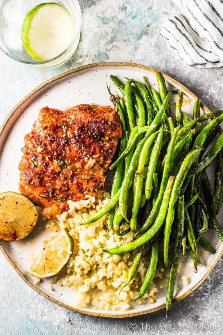 Honey glazed salmon on a plate with green beans on the side.