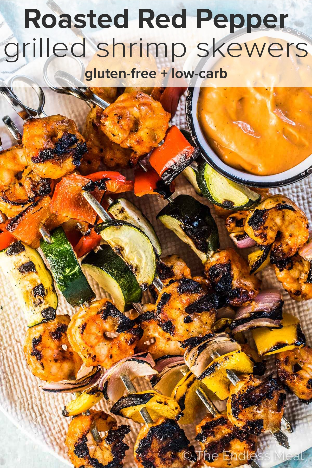 Grilled shrimp skewers piled high on a plate with roasted red pepper dip on the side and the recipe title at the top of the picture.