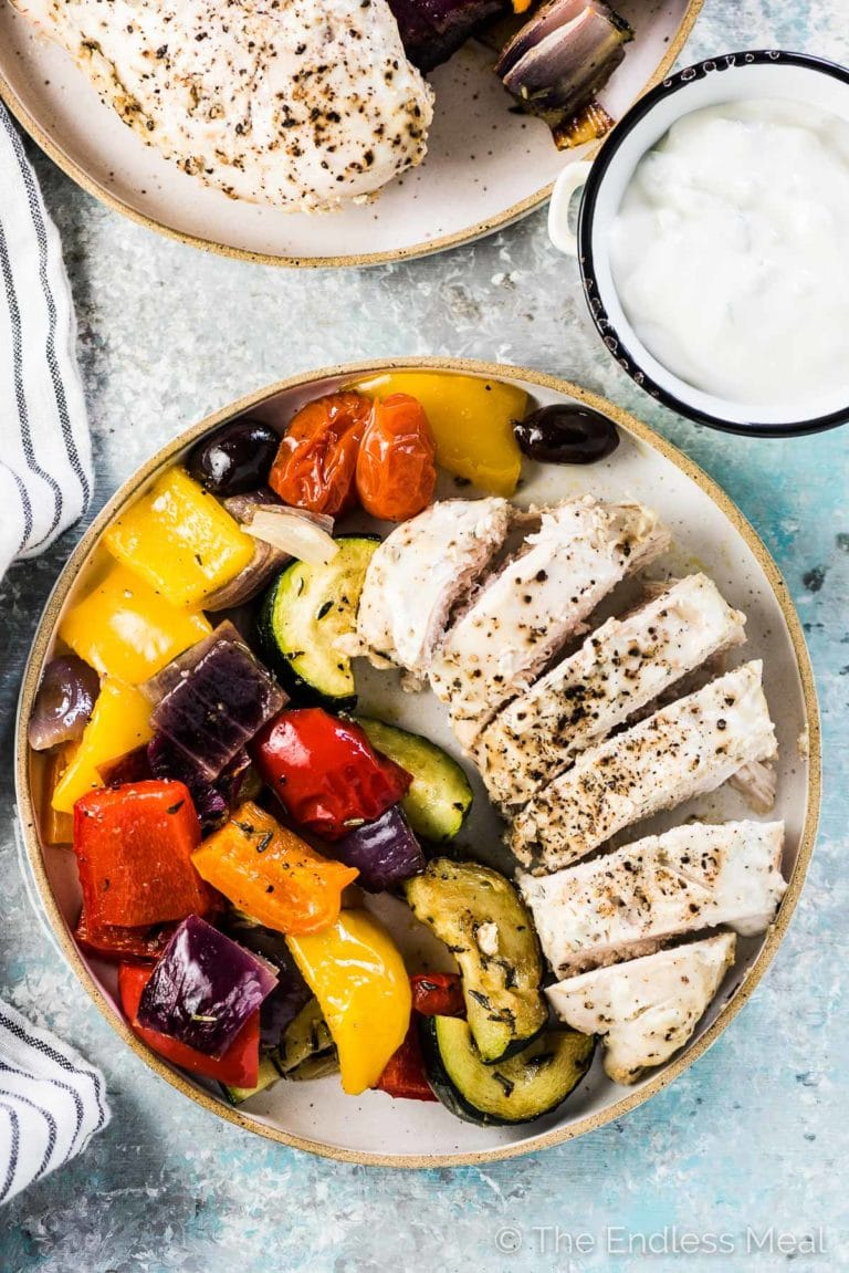 Tzatziki chicken breast sliced on a plate and surrounded by roasted Greek vegetables and black olives.
