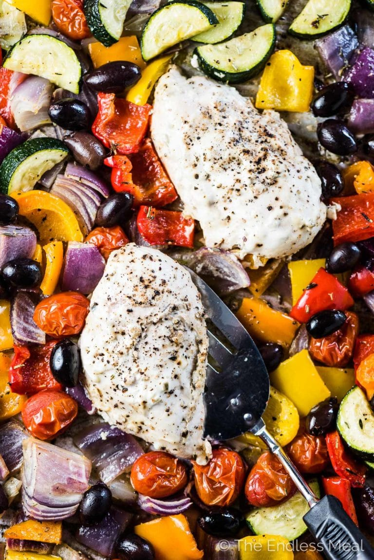 Two tzatziki chicken breasts on a baking sheet surrounded by roasted Greek veggies.