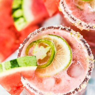 2 glasses of watermelon margarita with a watermelon slice on the side and a lime and jalapeno slice on top.