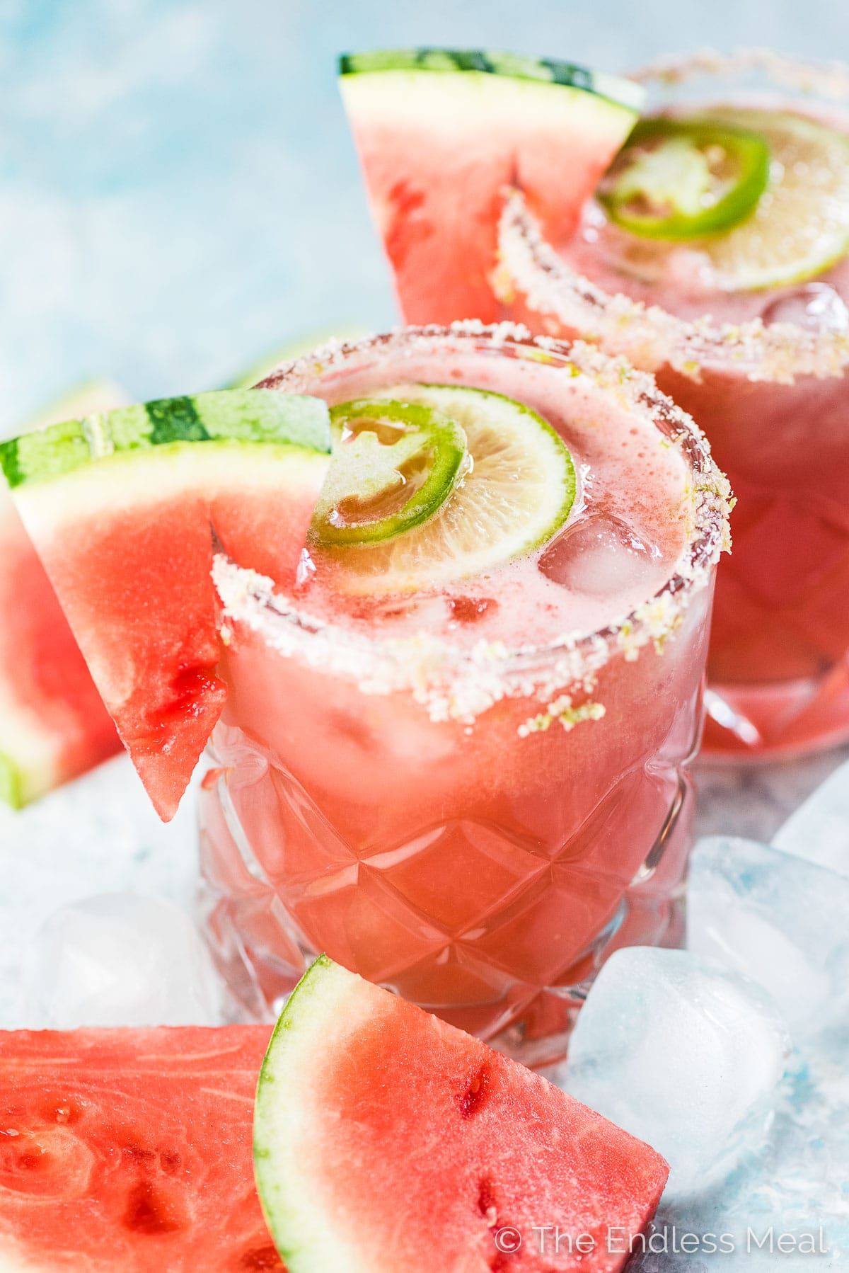 Two glasses of pink margarita with watermelons on the side.