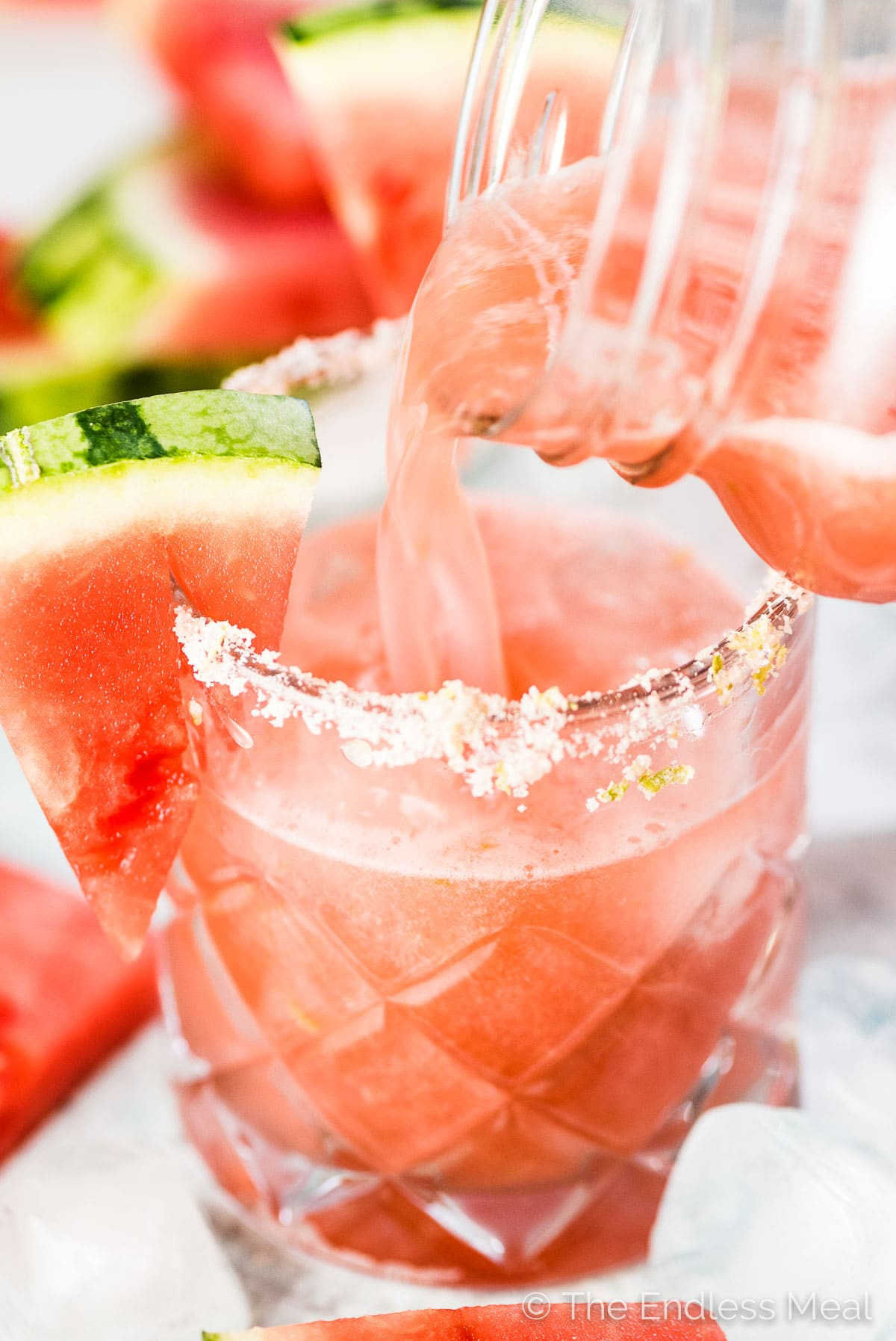 Pink watermelon margarita being poured into a salt rimmed glass.