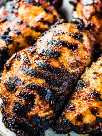 4 juicy grilled chicken breast on a plate with tasty grill marks all over them.