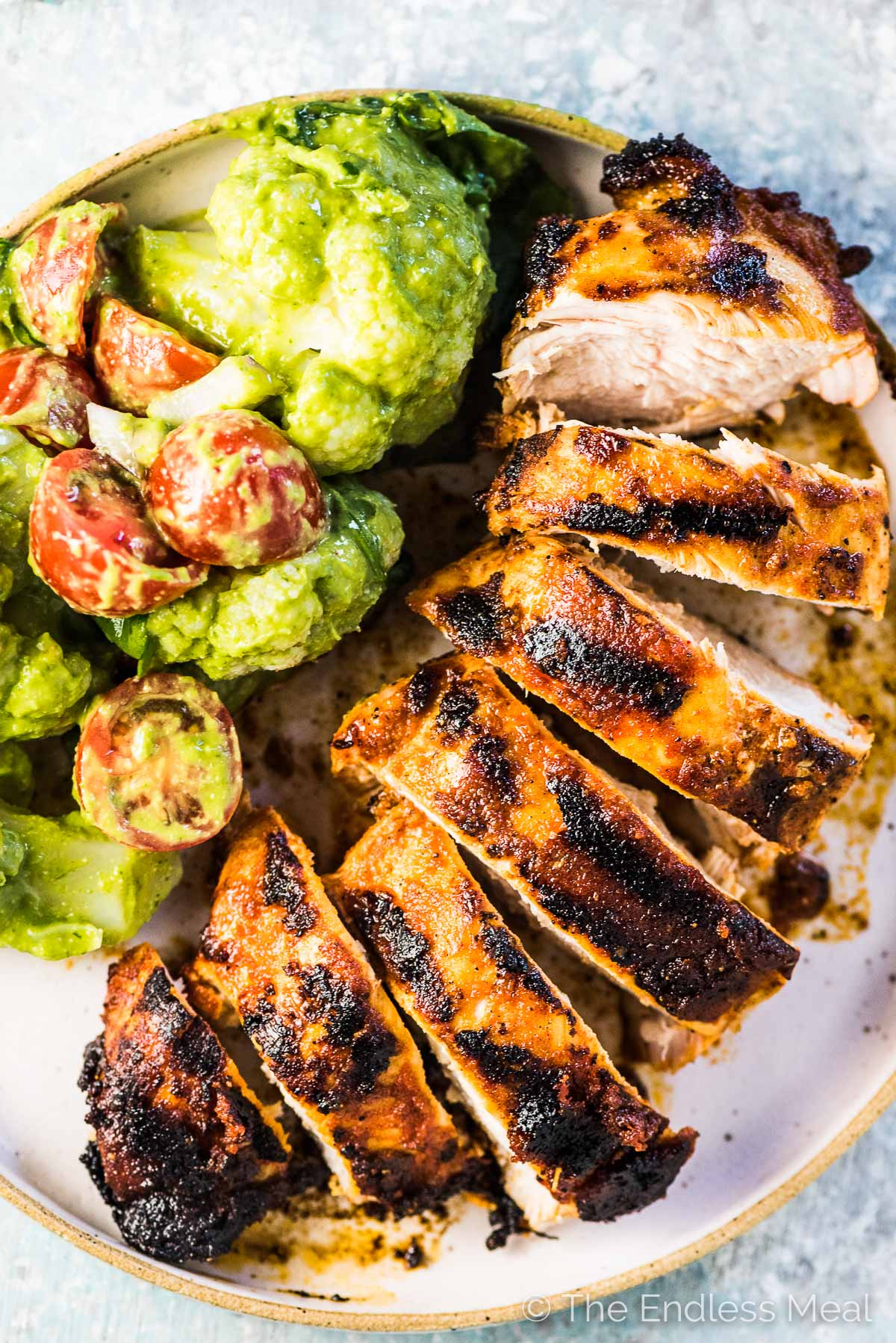 A juicy grilled chicken breast sliced on a plate beside cauliflower salad.