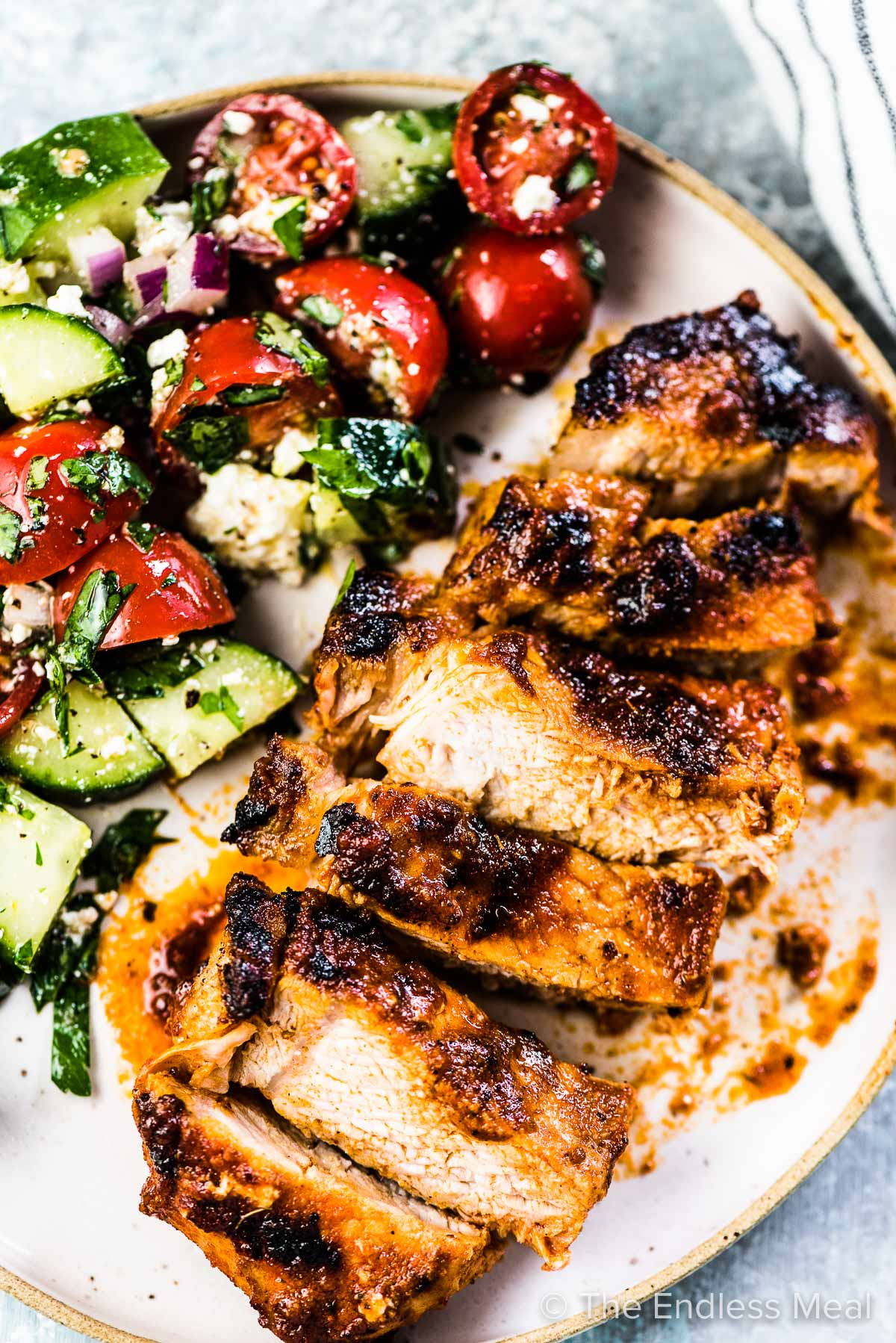 Sliced barbecue pork chops on a dinner plate with a side of tomato cucumber salad.