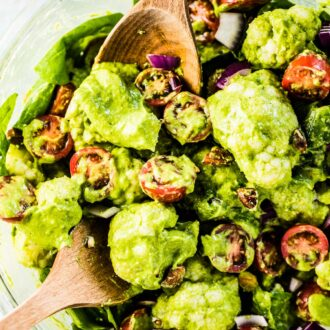 A glass bowl filled with cauliflower salad, cherry tomatoes, and lots of creamy avocado pesto.