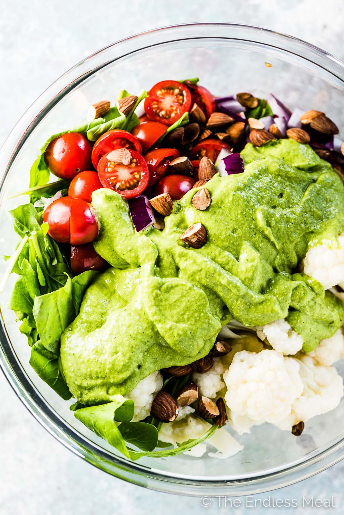 This cauliflower salad recipe in a glass bowl with avocado pesto salad dressing poured over the top.