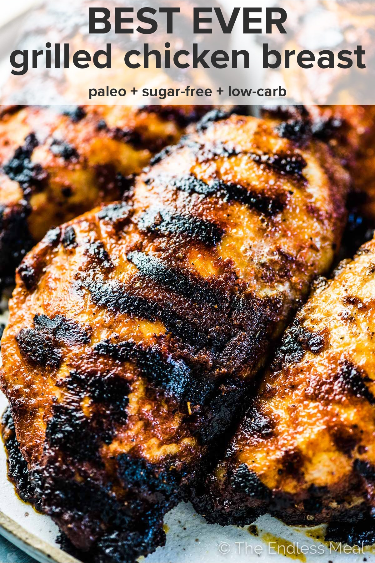 Juicy grilled chicken breast on a plate with the recipe title at the top of the picture.