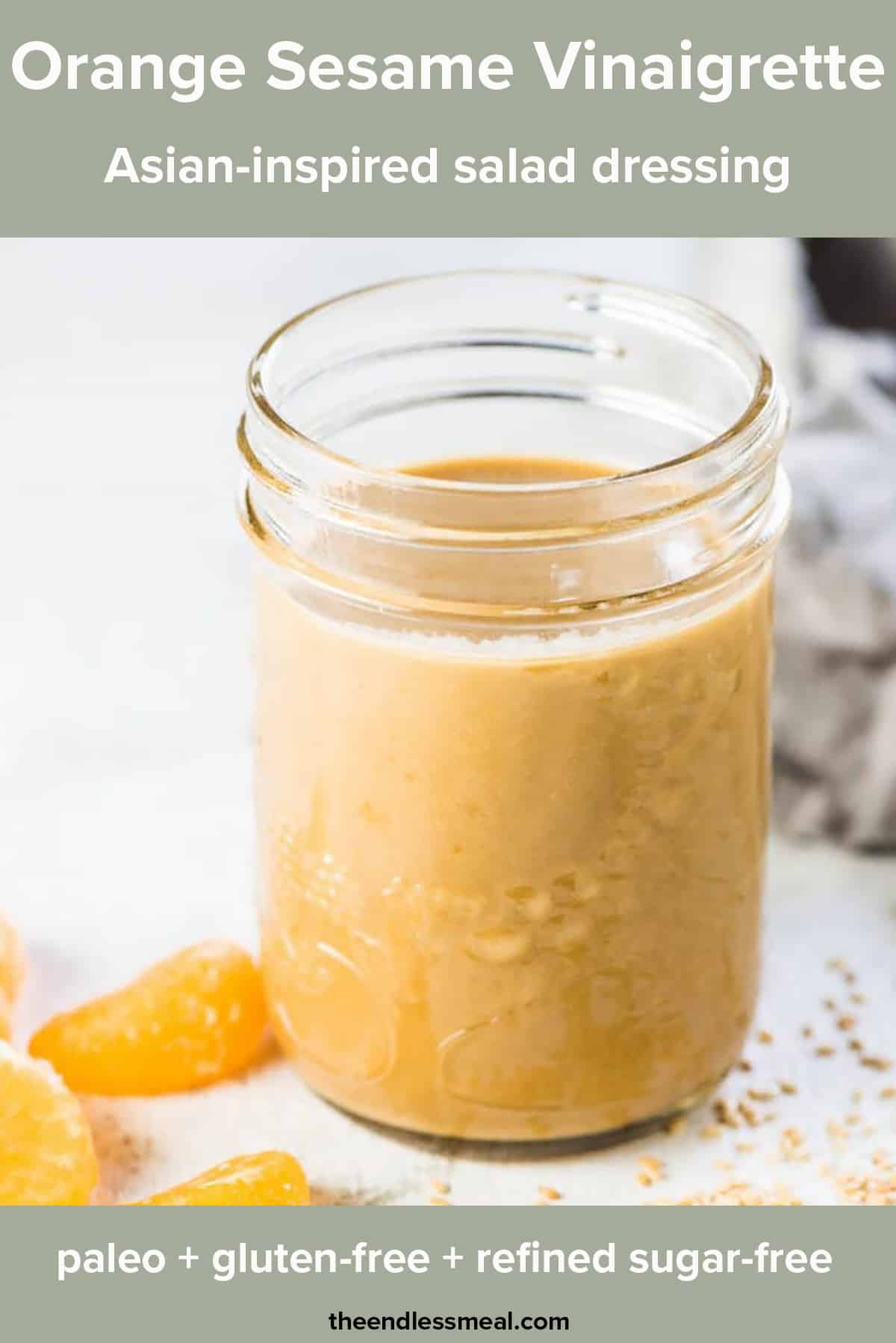 A glass jar of Sesame Orange Vinaigrette with some orange slices beside it and the recipe title on top of the picture.
