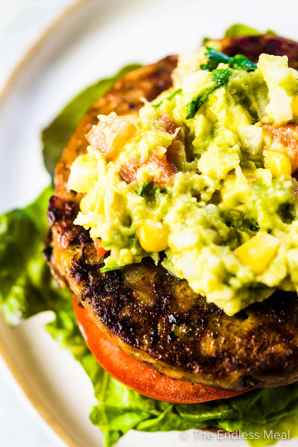 Sol Cuisines's Portobello Mushroom & Quinoa Burger on a bun topped with guacamole.
