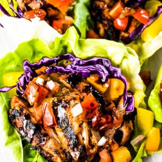 Three bruschetta chicken lettuce wraps on a plate with balsamic vinegar drizzled over the top.