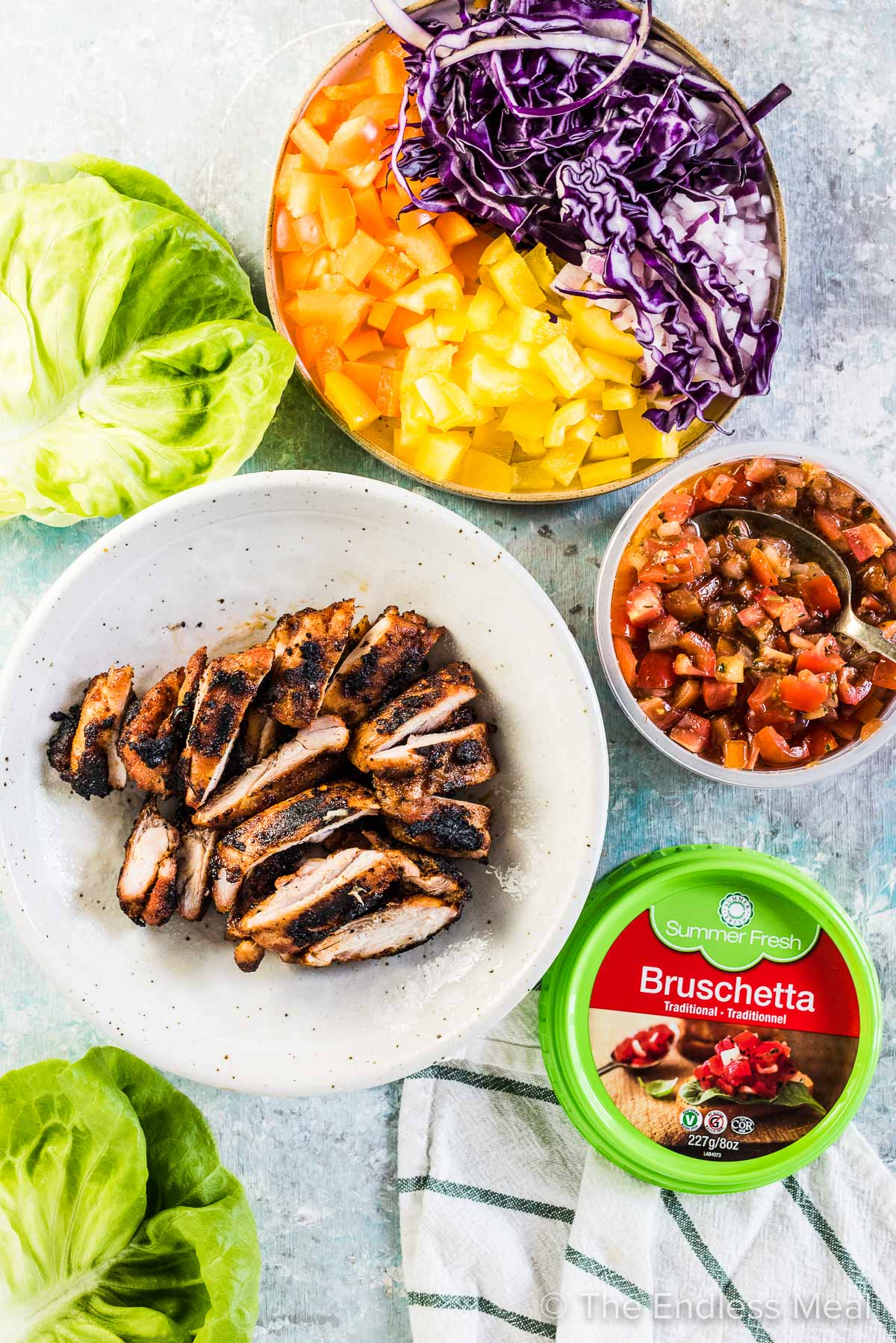 All the ingredients to make bruschetta chicken lettuce wraps laid out on a table.