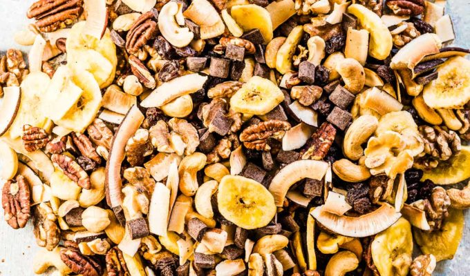 All the healthy trail mix ingredients mixed together on a blue board.