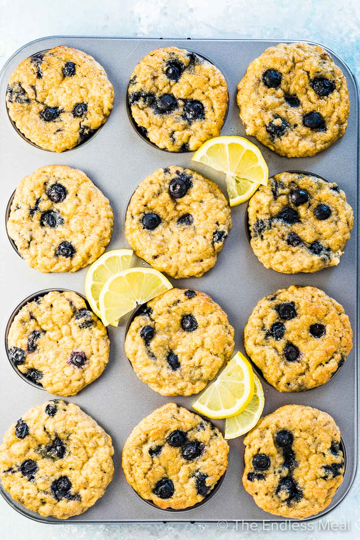 A muffin tin with lemon blueberry paleo muffins.