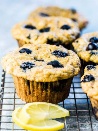 Paleo blueberry muffins on a cooling rack with a few lemon slices.