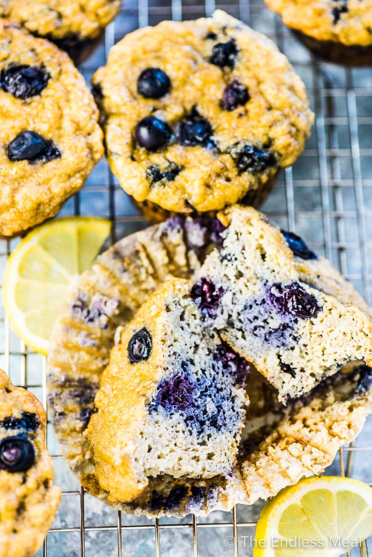 A paleo blueberry muffin cut in half with lots of fresh blueberries inside.