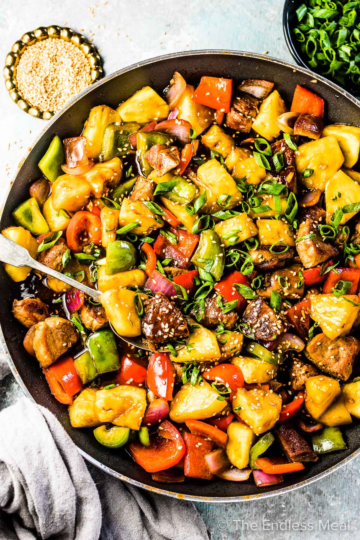 A pan filled with pineapple pork stir fry on a table with sesame seeds and green onions beside it.