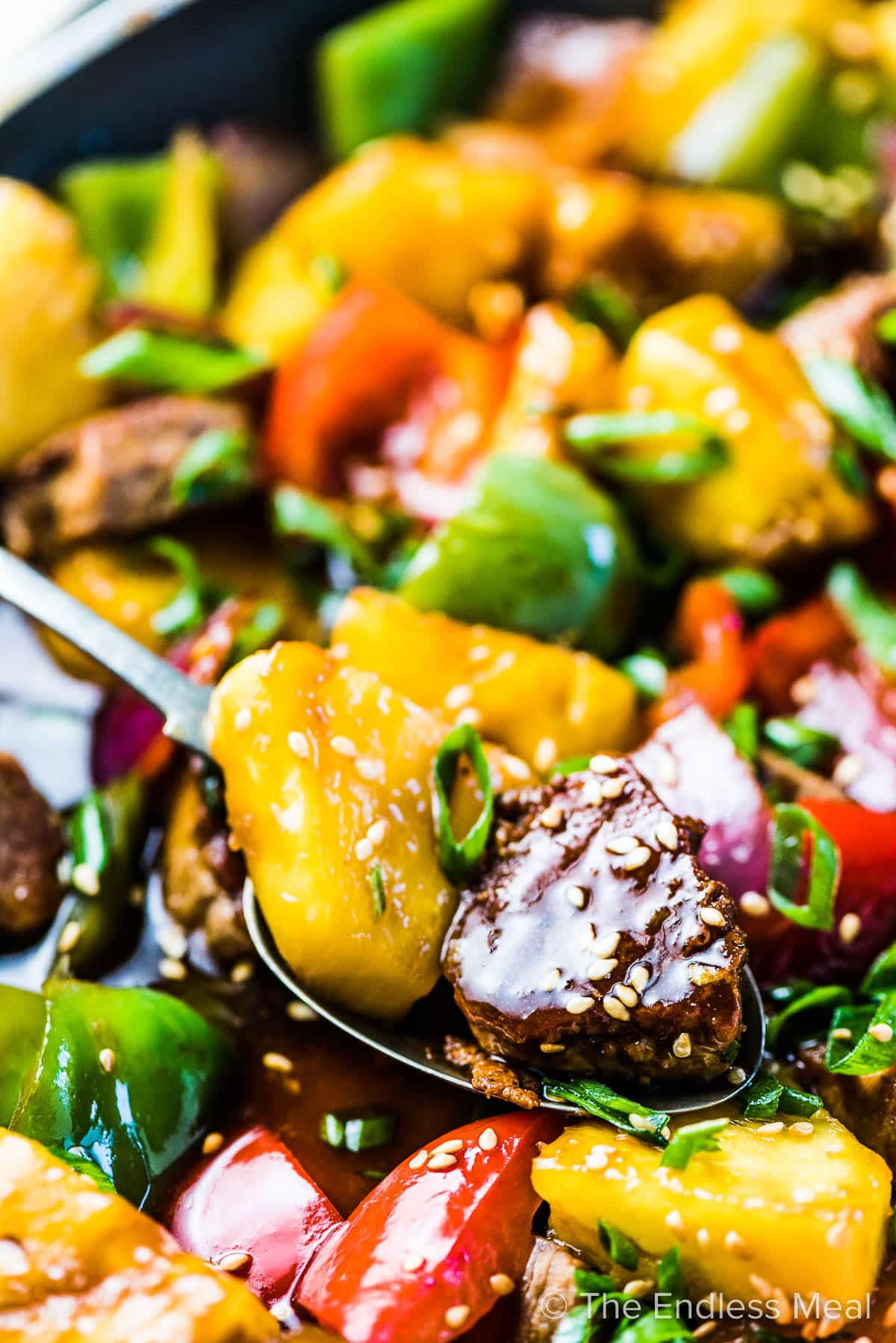 A close up of a spoon scooping some of this pork stir fry recipe.