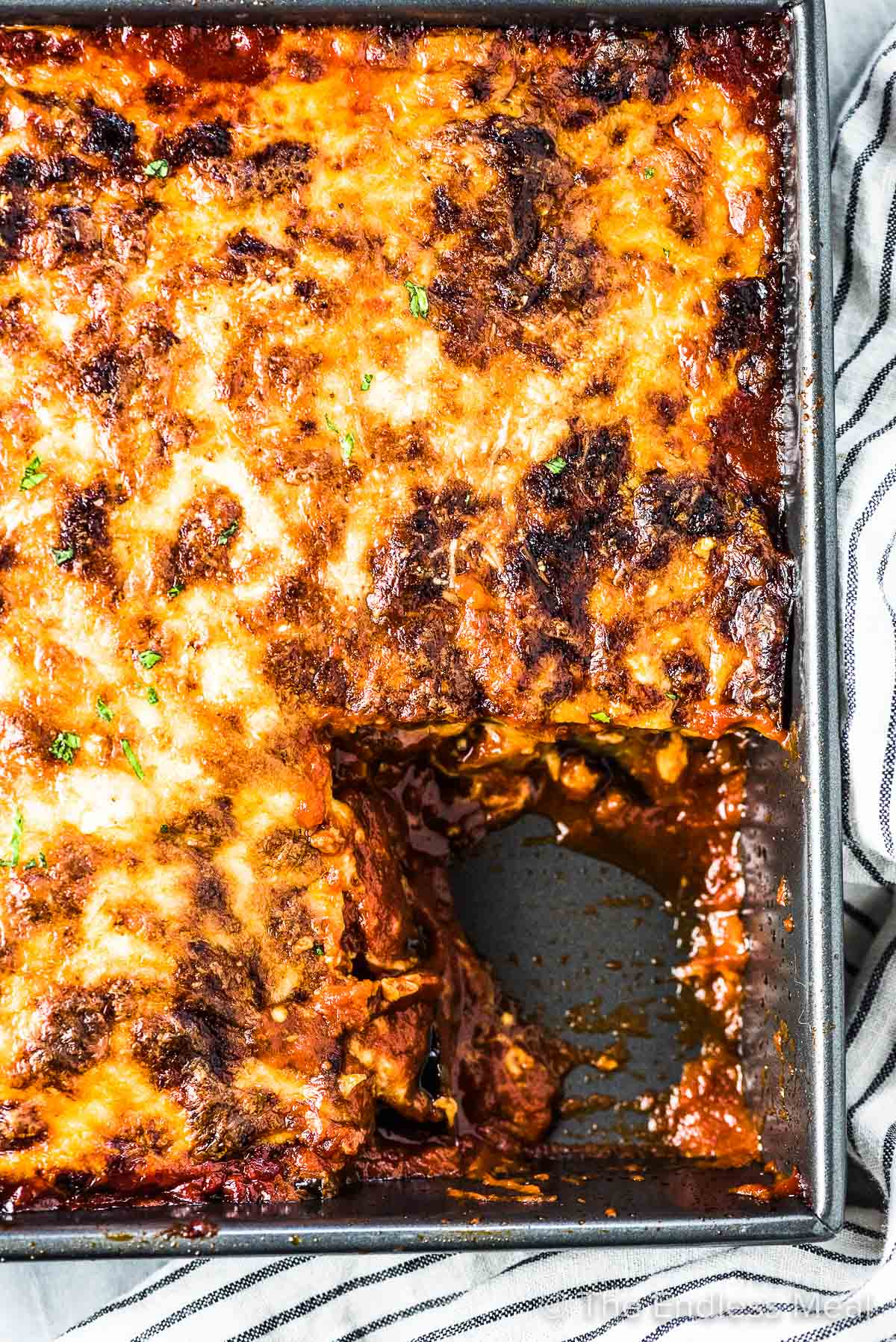 A pan of this easy eggplant parmesan recipe with one scoop taken out.