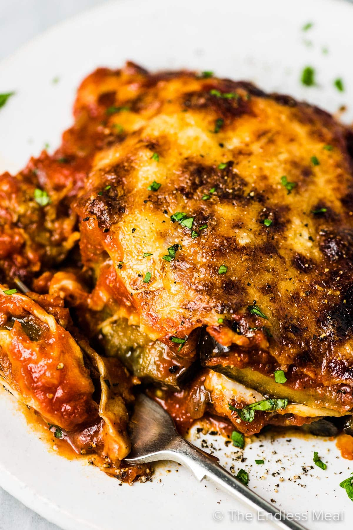 A close up of this easy eggplant parmesan on a white plate with a fork taking a bite.