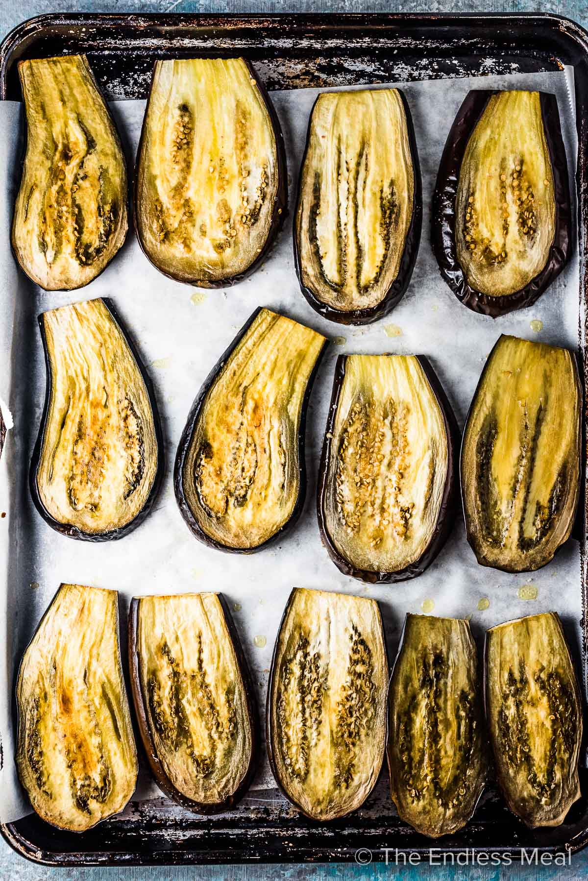 Unbreaded baked eggplant slices on a baking sheet.