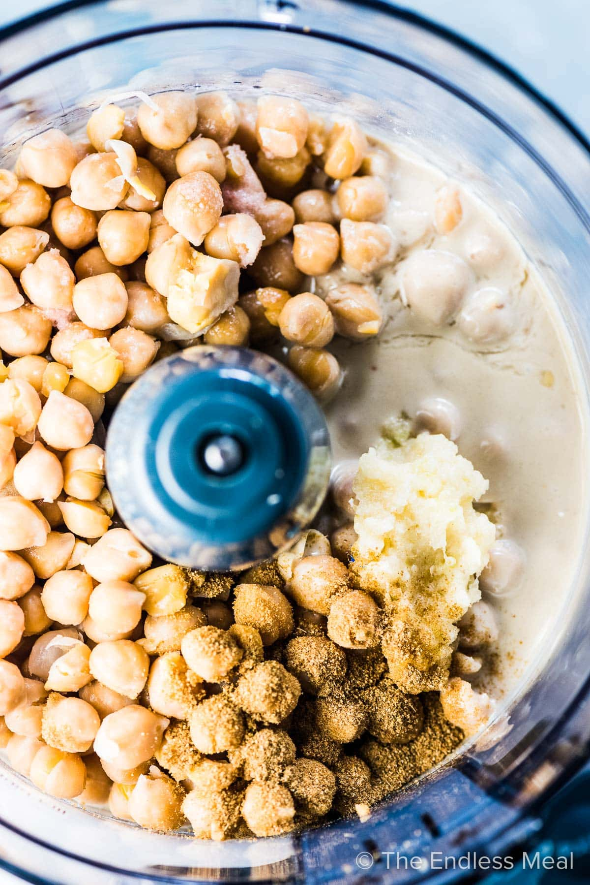 All the ingredients for this hummus recipe in a food processor.