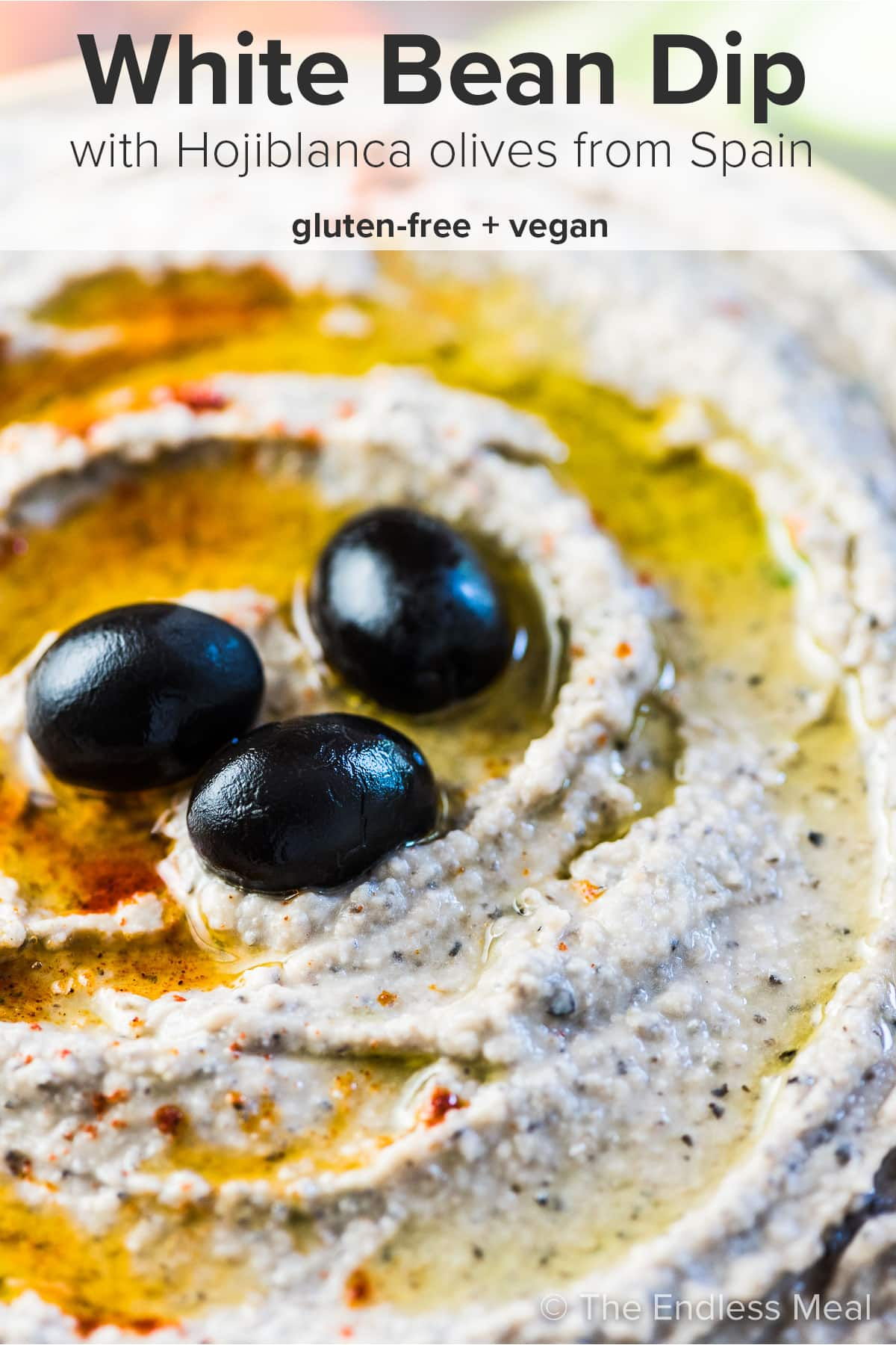 A close up of this olive and white bean dip with the recipe title at the top of the picture.