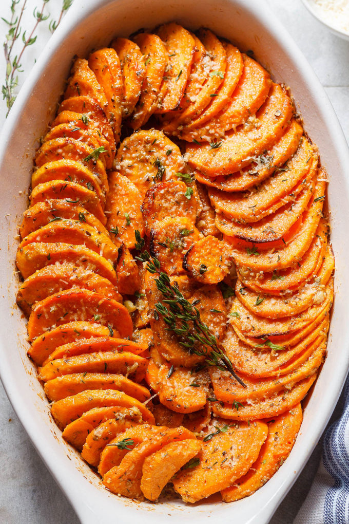 A white baking dish with layers of roasted sweet potatoes.
