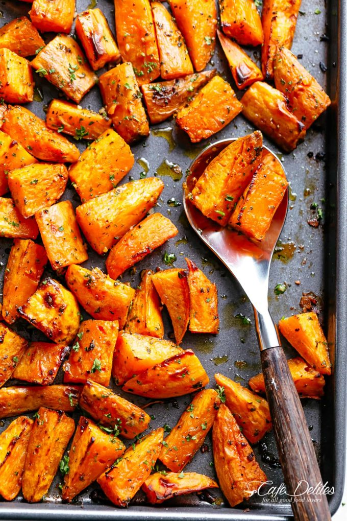 A baking sheet filled with roasted sweet potatoes with a serving spoon taking a scoop.