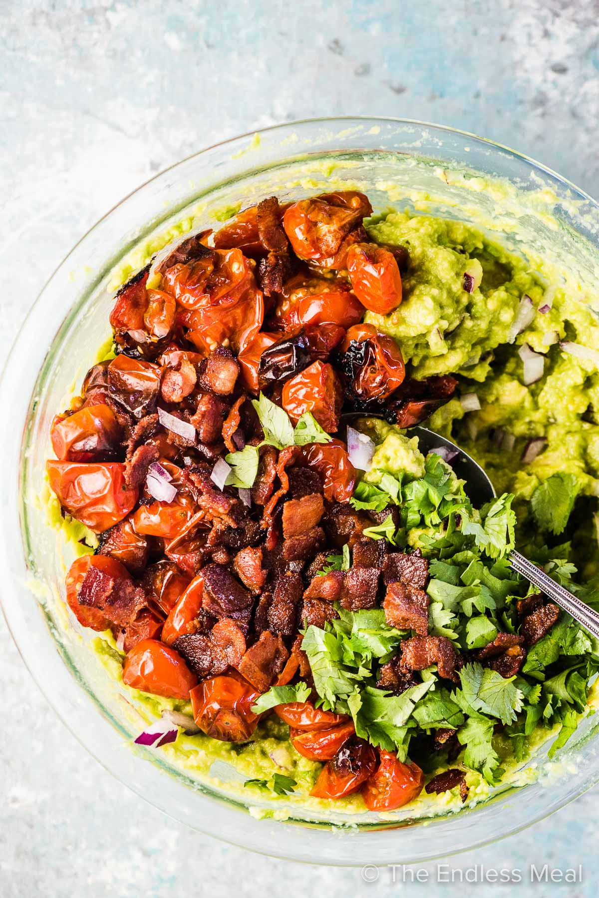 A mixing bowl with mashed avocados, roasted tomatoes, and crispy bacon.