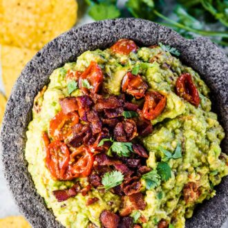 Bacon guacamole in a serving bowl with chips on the side.