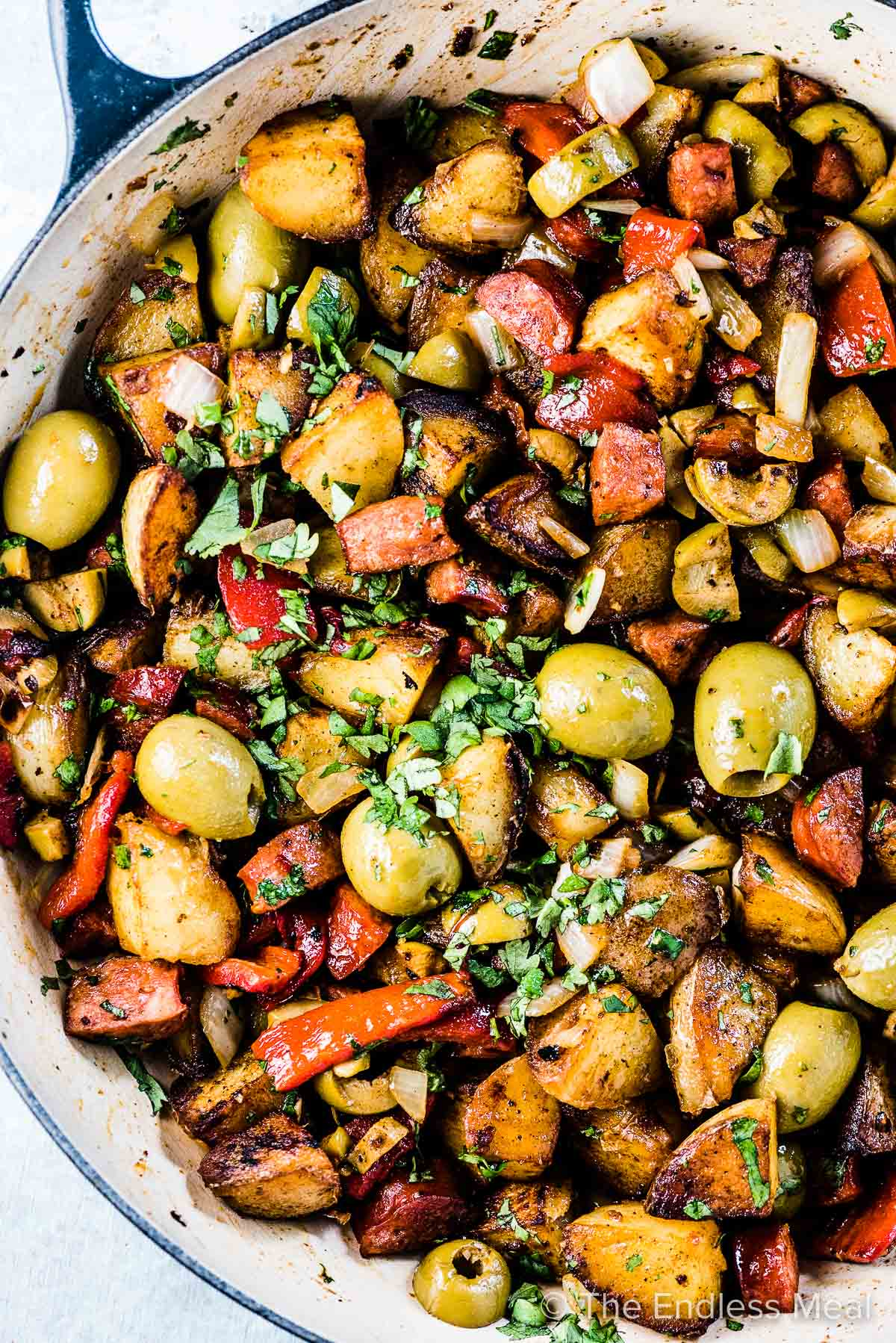 A skillet with pan fried breakfast potatoes with olives, chorizo, and roasted red peppers.