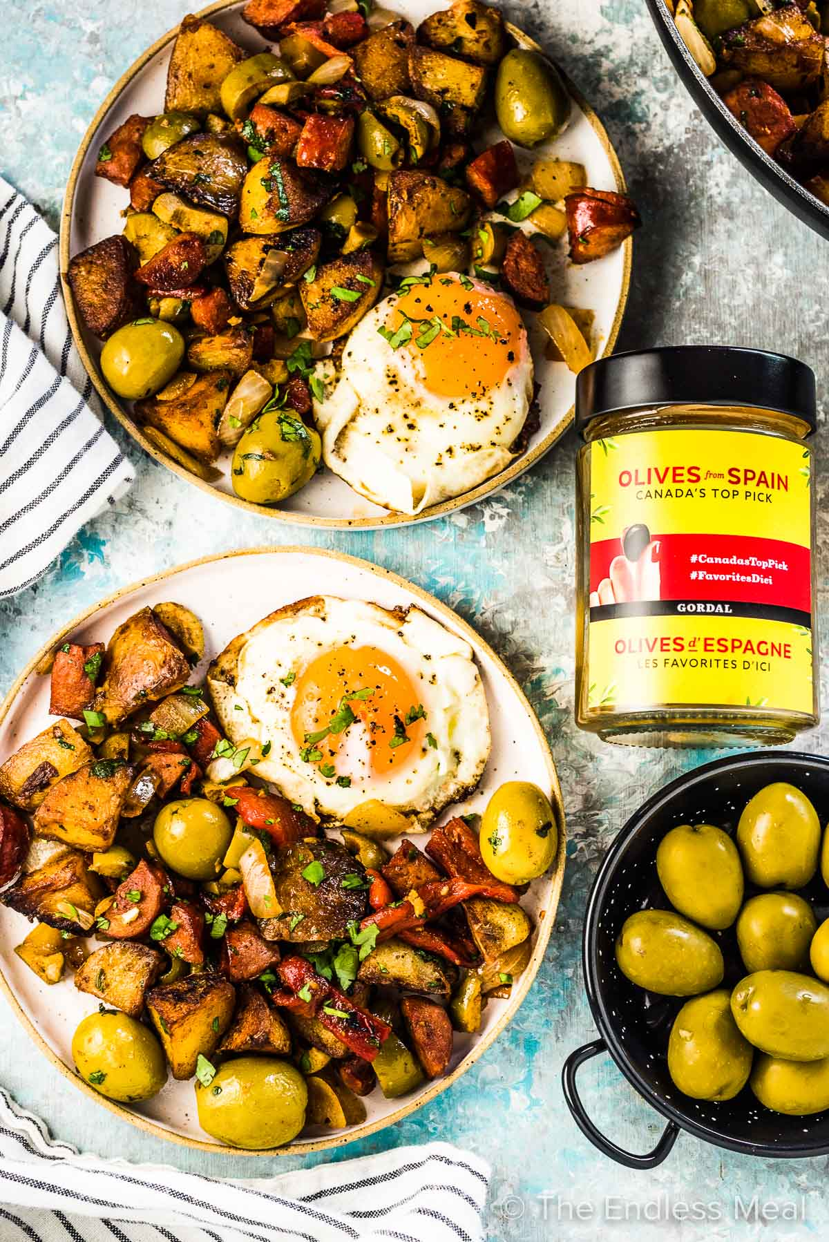 Two plates filled with Spanish breakfast potatoes and fried eggs with a jar of Spanish Hojiblanca olives beside them.