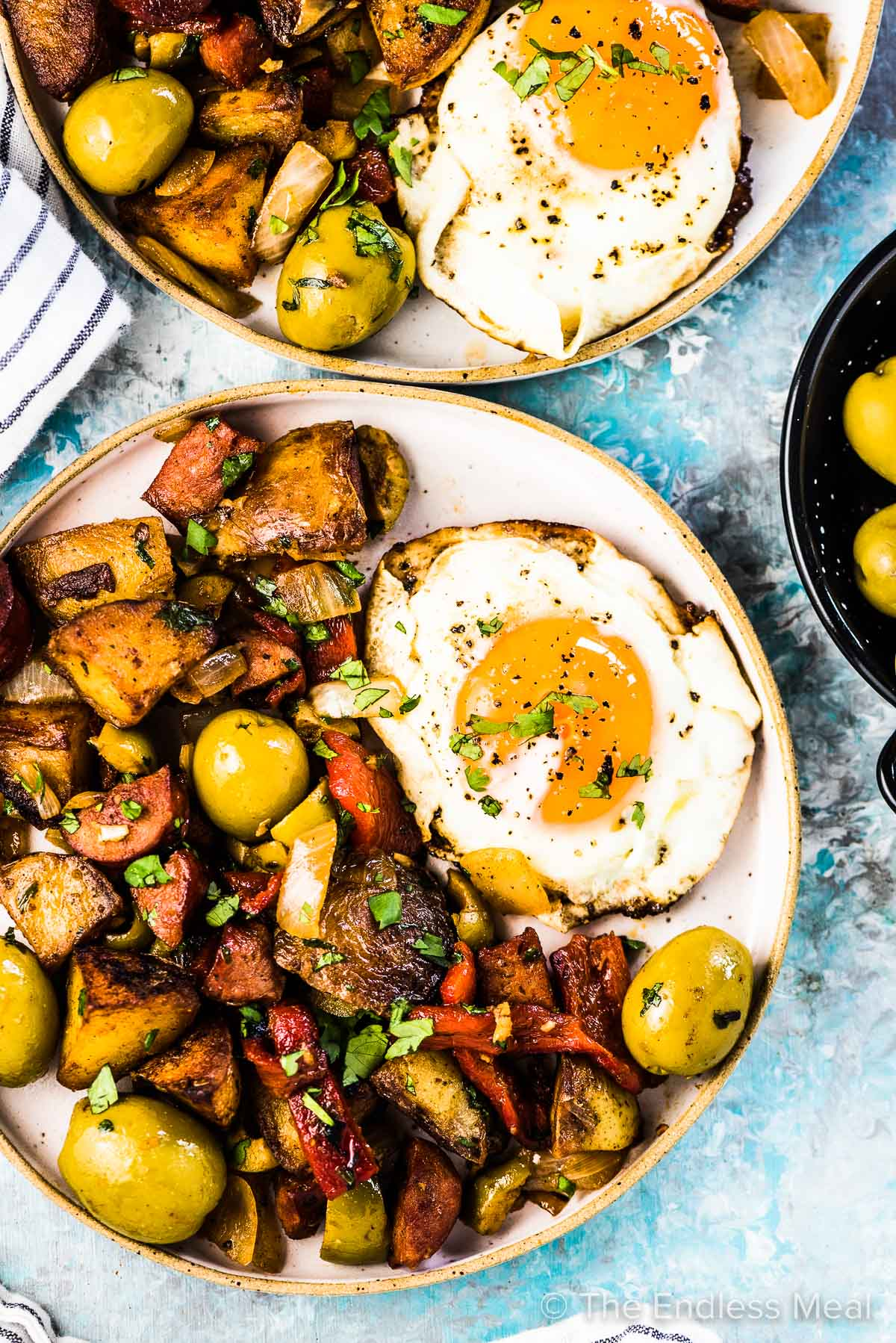 Two plates filled with Spanish breakfast potatoes and a fried egg.