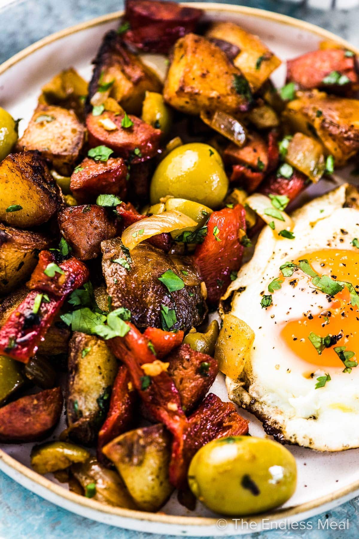 A close up of this Spanish breakfast potatoes recipe on a plate with a fried egg beside it.
