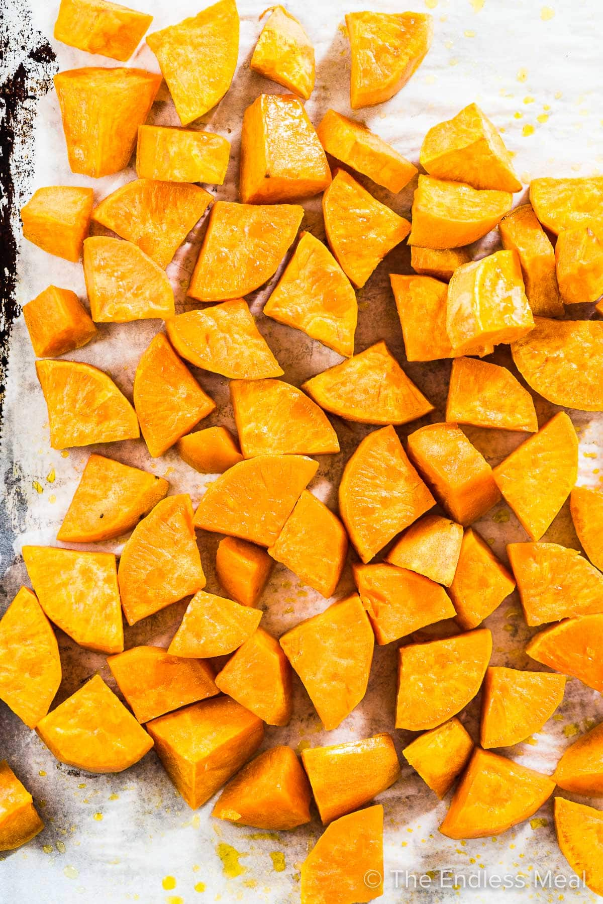 Roasted sweet potato cubes on a baking tray.
