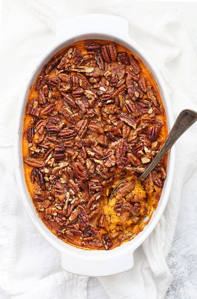 A white baking dish filled with sweet potato casserole and topped with pecans.