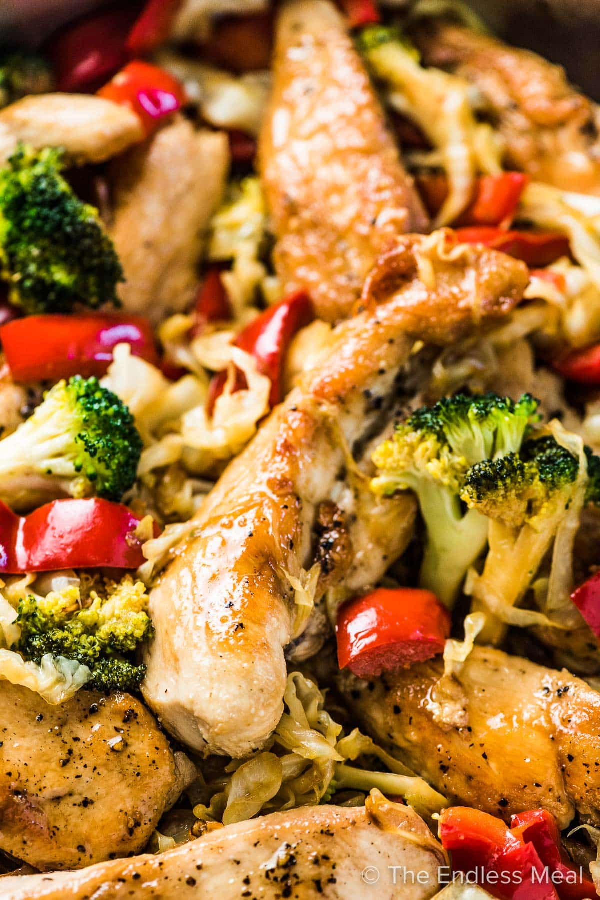 A close up of a piece fo chicken in this cabbage stir fry recipe.