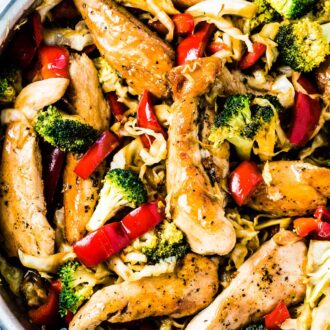 A frying pan full of chicken cabbage stir fry with red peppers and broccoli.