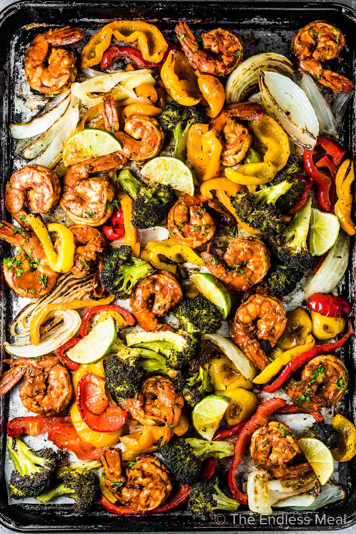 A baking sheet with lots of roasted veggies and some chili lime shrimp.