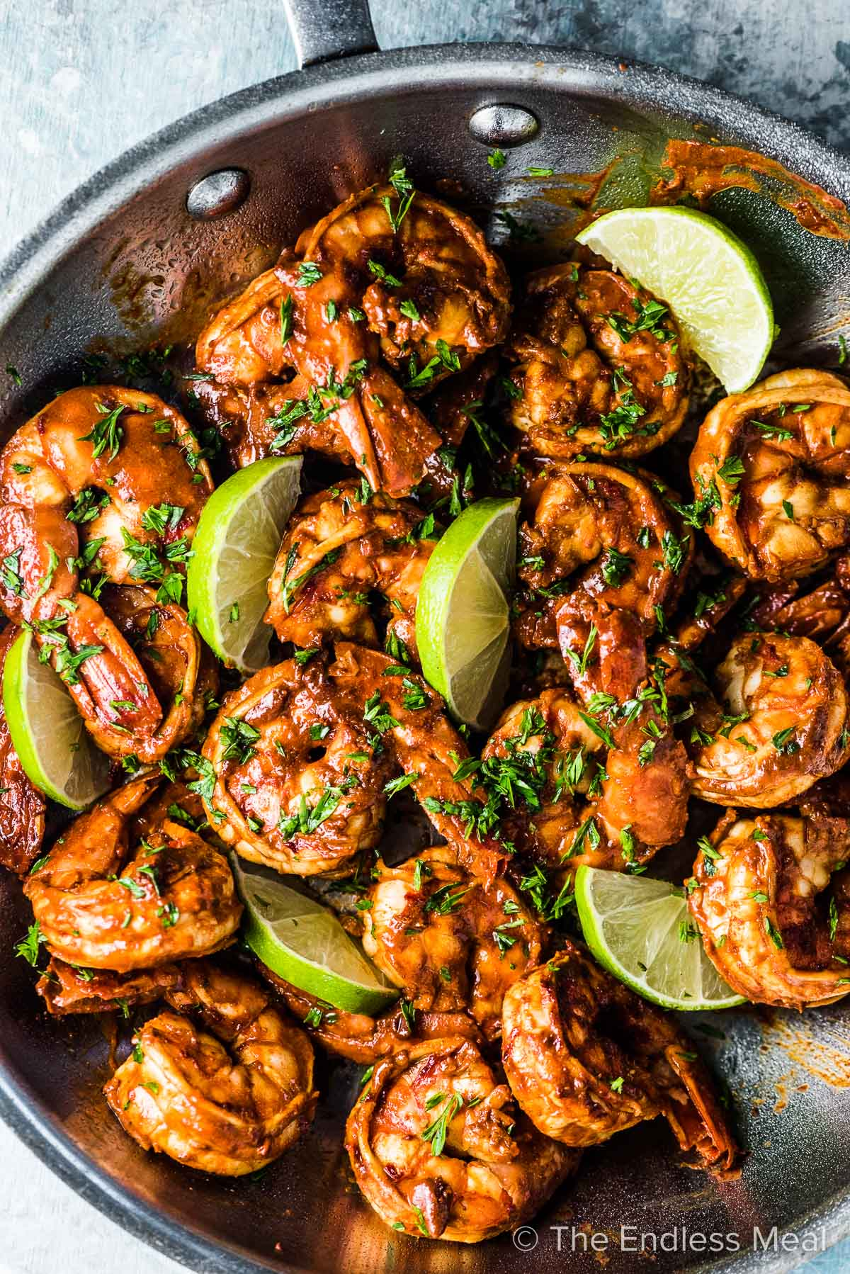Chili lime shrimp in a pan with lime slices.