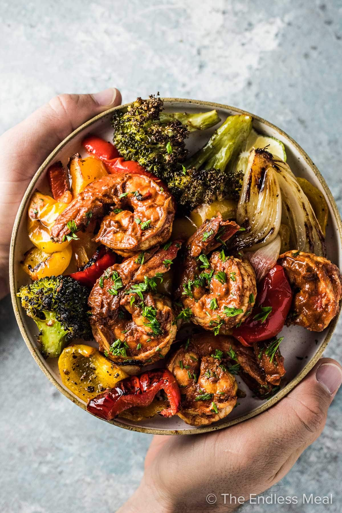 Hands holding a plate of chili lime shrimp with lots of veggies.